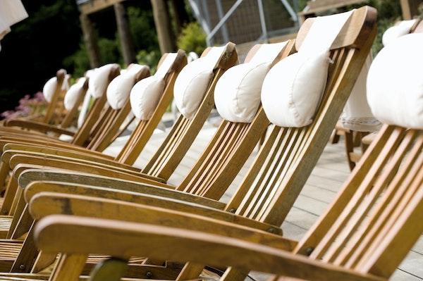 Liegestühle aus resistentem Holz mit weißen Kopfkissen
